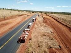 Pra cego ver: Imagem aérea de rodovia asfaltada com alguns carros enfileirados à margem e, ao lado, trecho sem asfalto em construção. Fim da descrição.