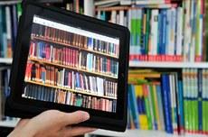 Pra cego ver: uma mão segura um tablete com imagens de livros expostos em fileiras e, ao fundo, uma imagem de prateleiras com vários livros. Fim da descrição.