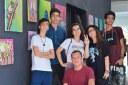 Estudantes participantes do projeto de Extensão: Colorindo o Mundo, em frente às obras produzidas por eles. Fim da descrição.