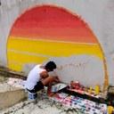 Pra cego ver: estudante agachado enfrente a um muro, com pincéis na mão, concluindo uma pintura que se assemelha à figura do sol. Potes de tintas estão ao seu lado. Fim da descrição.