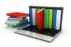 Pra cego ver: vários livros empilhados ao lado de um notebook com livros e um saltando à tela para fora. Fim da descrição.